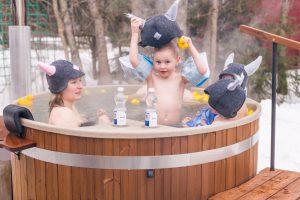 Spelende kinderen in hottub met mutsen op